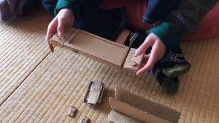 Kleiner Junge bastelt Nintendo Switch aus Pappkarton